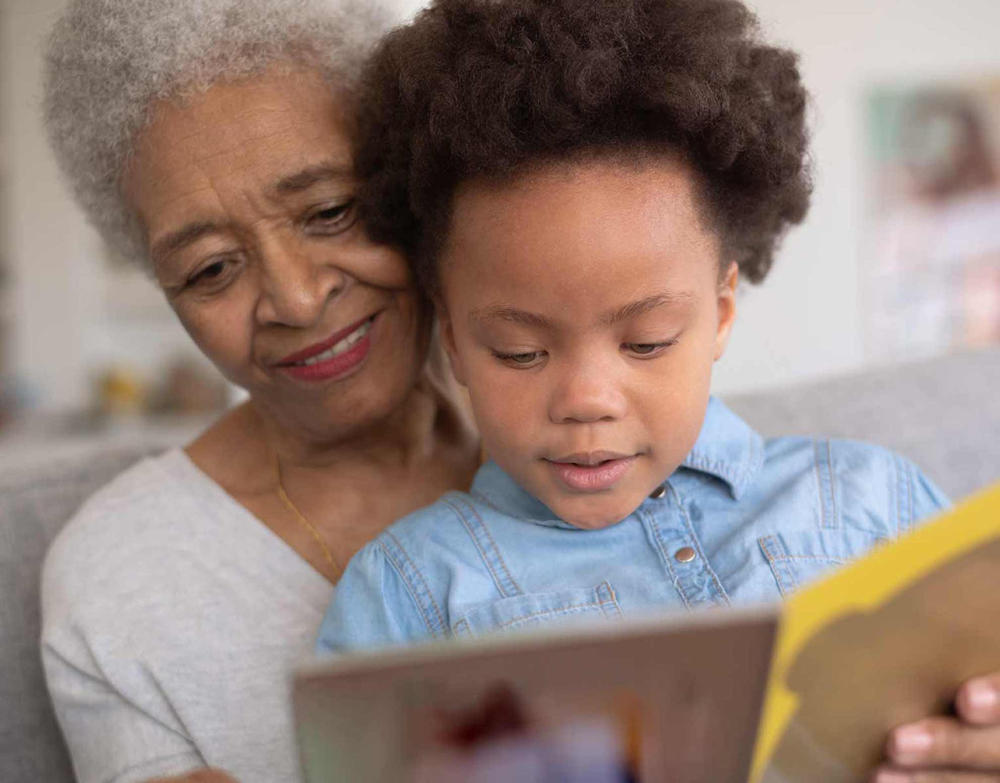 Photo of grandmother and her granddaughter reading a book
